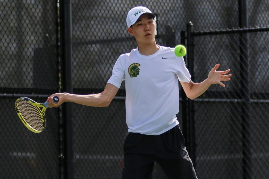 Jayden Shin '23 stares down the ball as he prepares to swing against City High at the Hawkeye Tennis and Recreation Center on April 29.