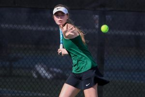 Ella De Young '23 eyes the ball as she waits to take a swing against City High at the Hawkeye Tennis and Recreation Center on April 29.
