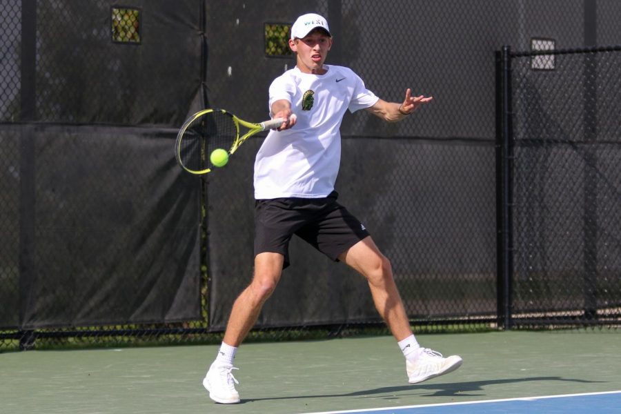 Eli Young '21 returns the ball for a point against City High at the Hawkeye Tennis and Recreation Center on April 29.