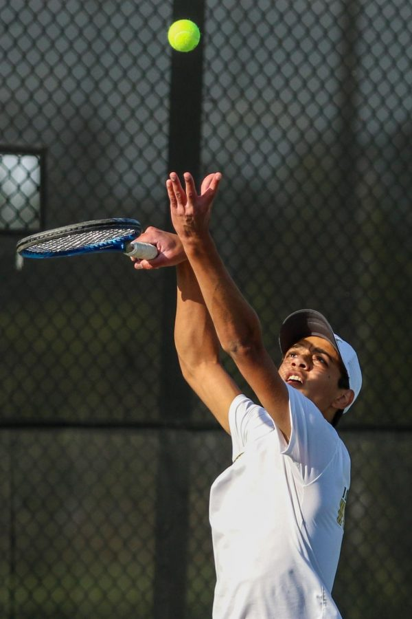 Luca Chackalackal '22 throws the ball into the air as he prepares to serve against City High at the Hawkeye Tennis and Recreation Center on April 29.