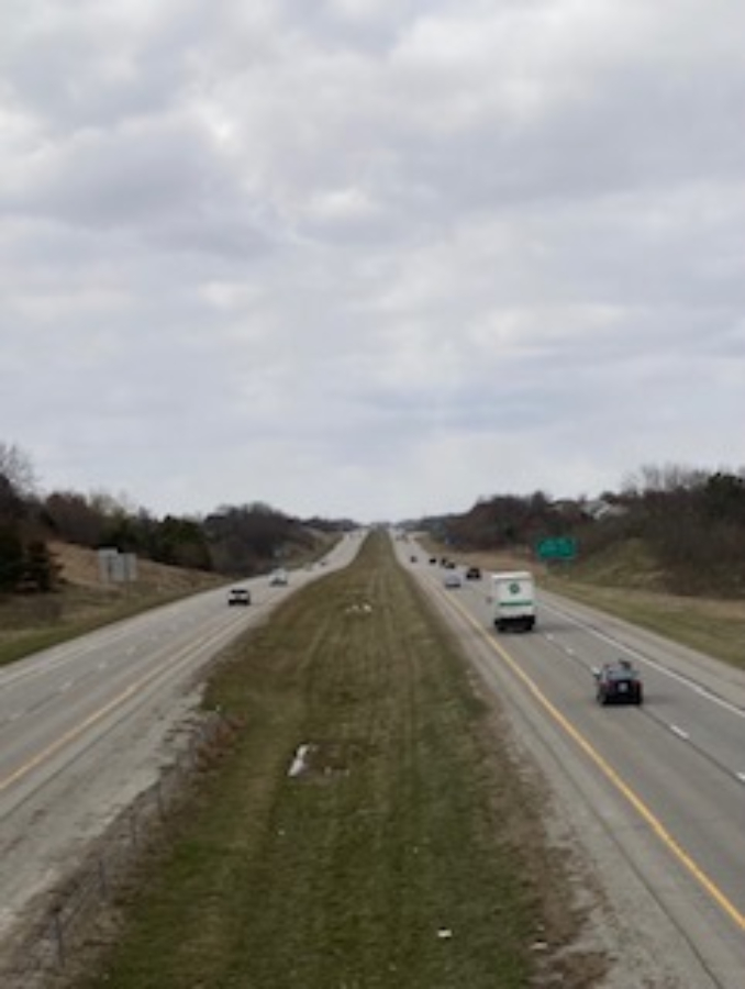 """Afternoon of March 31st, 2021 above highway 218, Rosenthal 24 takes a picture of traffic racing in below 50 degree weather. """"I tried to get a picture of movement through the line of the horizon, to seem as though theyre coming and going from who knows where."""