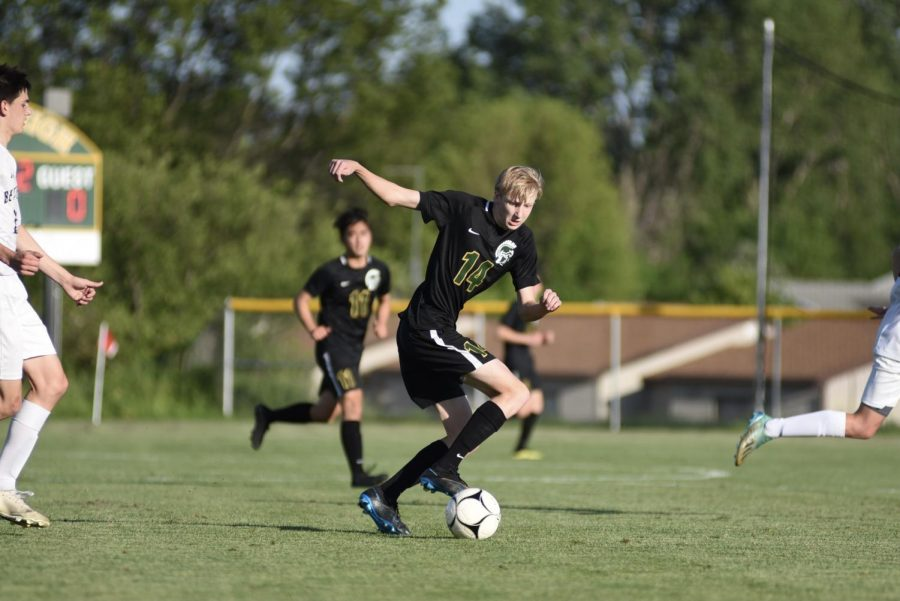 Brenden Klutts '21 turns the ball towards the Bettendorf goal on May 26.