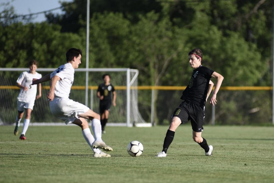 Matthew Steinbronn '21 attempts to move the ball through a Bettendorf defender on May 26.