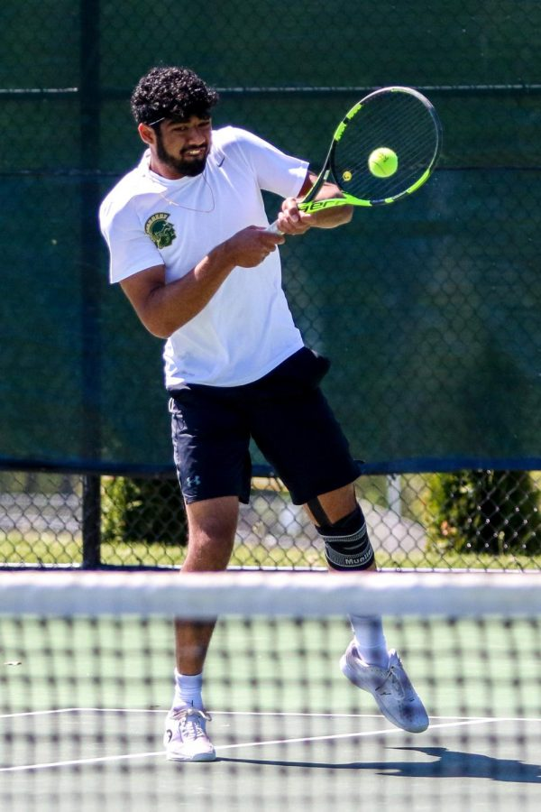 Mukundan Kasturirangan '21 makes a play on the ball while fighting through a knee injury at the IHSAA Boys District Tennis tournament on May 12.