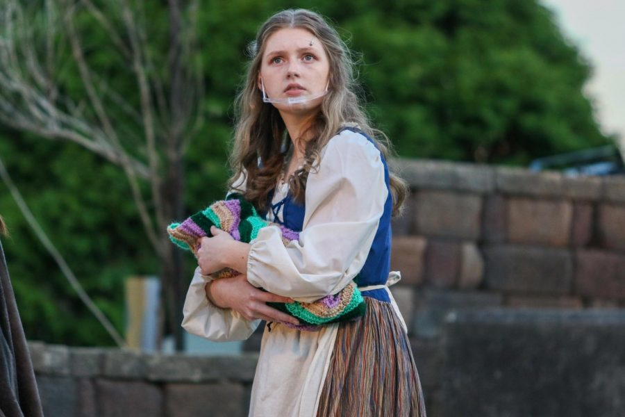 Sam Croco 22 looks off into the distance while preforming in Into the Woods in the West High courtyard on May 13.