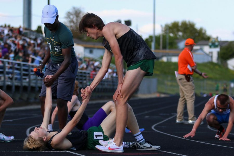 Alex McKane '22 and Steve Tembea '22 help up Seth Cheney '23 after he finished the 3200-meter race at the Class 4A district track and field meet on May 13.