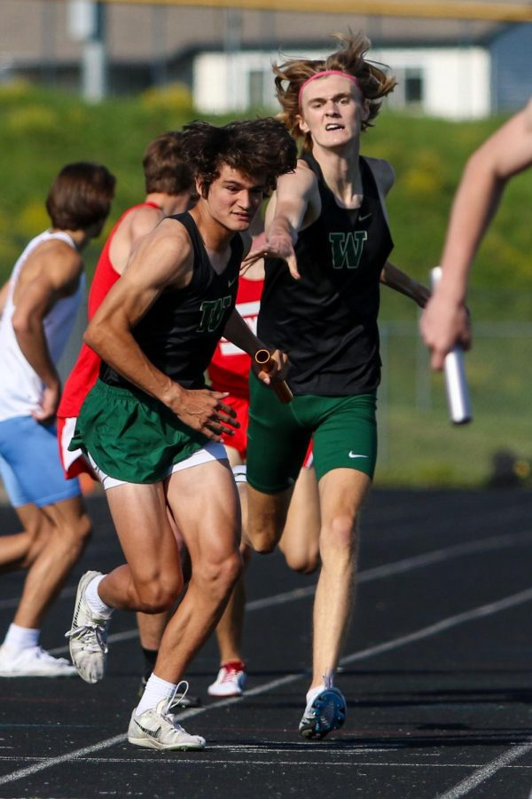 Ike Taylor '21 hands the baton off to Asher Overholt '23 while running the 4 by 800-meter relay at the Class 4A district track and field meet on May 13.