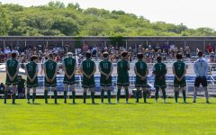 The boys soccer team stands while starters are announced before playing Pleasant Valley in the state championship game on June 5 in Des Moines.
