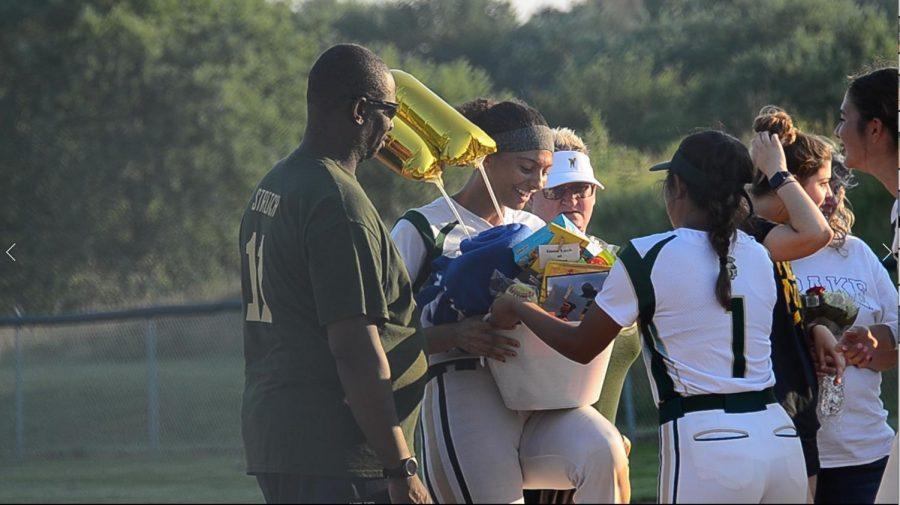 Teammate Tamiah Teran 23 hands off a basket to senior Liv Williams between games.