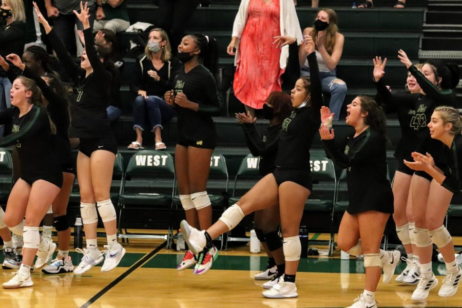 The West High Volleyball team cheers for their teammates as they get a point.