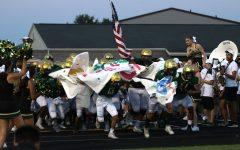 The Trojans break through a poster as they run onto Trojan Field.