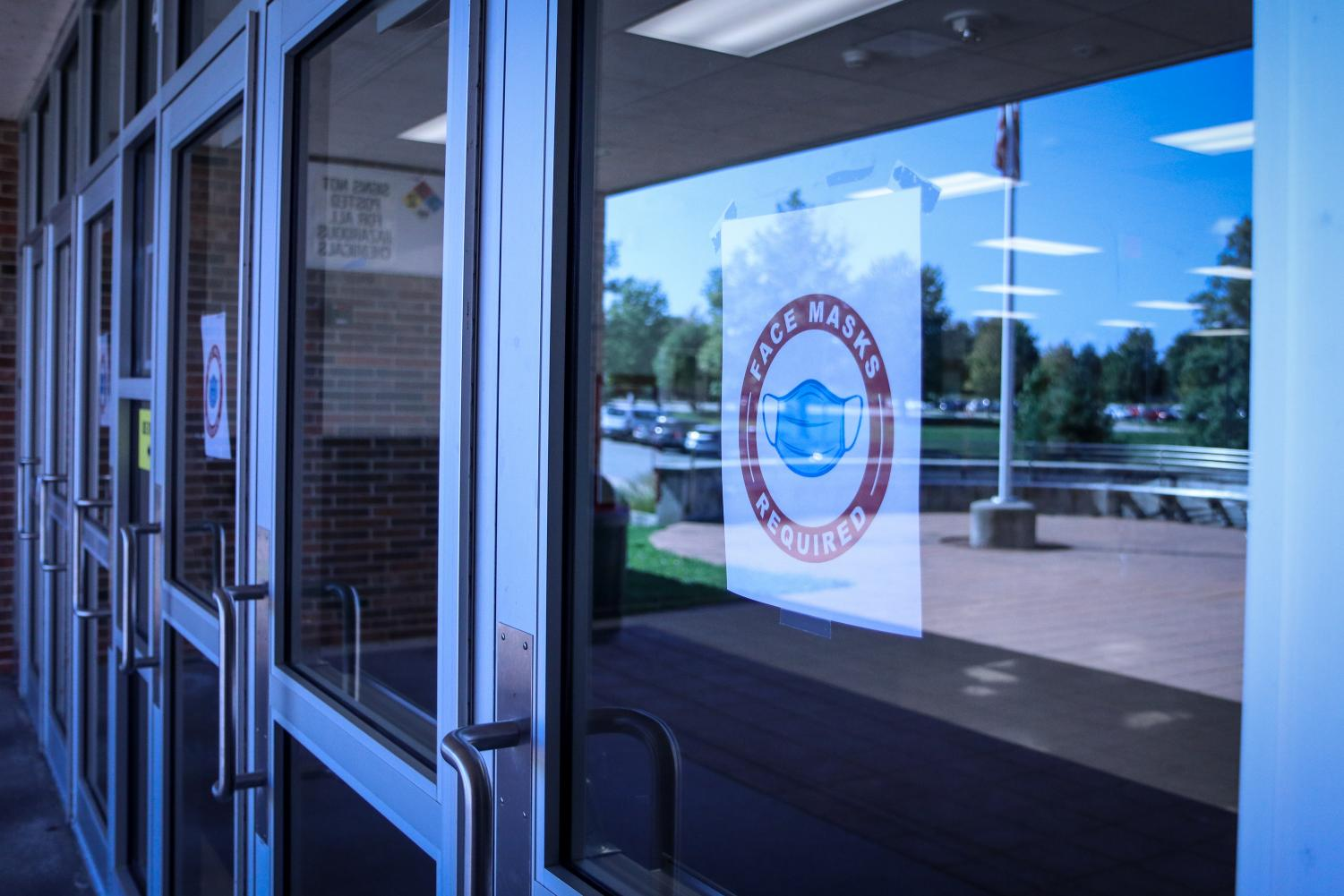A sign taped to the West High front door tells students, staff and visitors about the new mandate on Sept. 15.