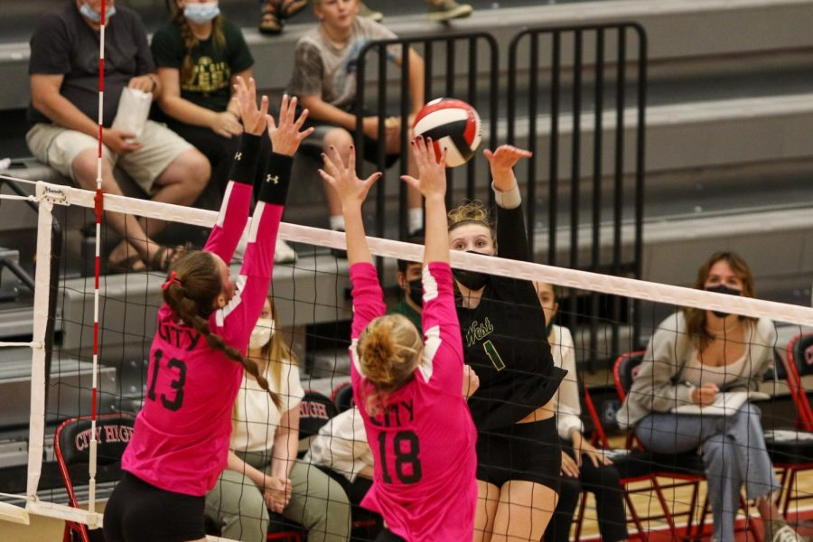 Emma Stammeyer 24 attempts to hit the ball past two City High blockers during the Battle for the Spike at City High on Sept. 30.