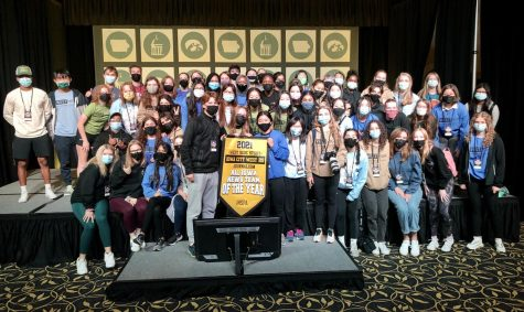 The 2021-2022 journalism team pose with  the News Team of the Year banner at the IHSPA state journalism conference at The University of Iowa on Oct. 21.