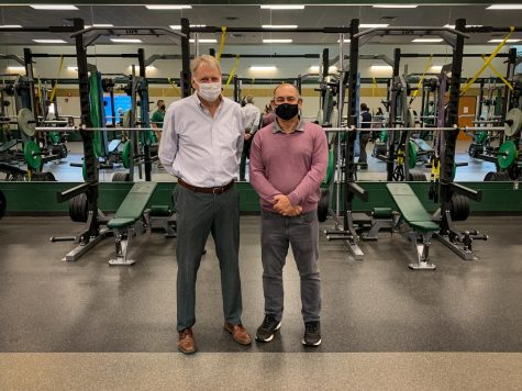Dr. Gregg Shoultz and Greg Hughes pose for a photo inside the West High weight room while touring the school on Oct. 26.